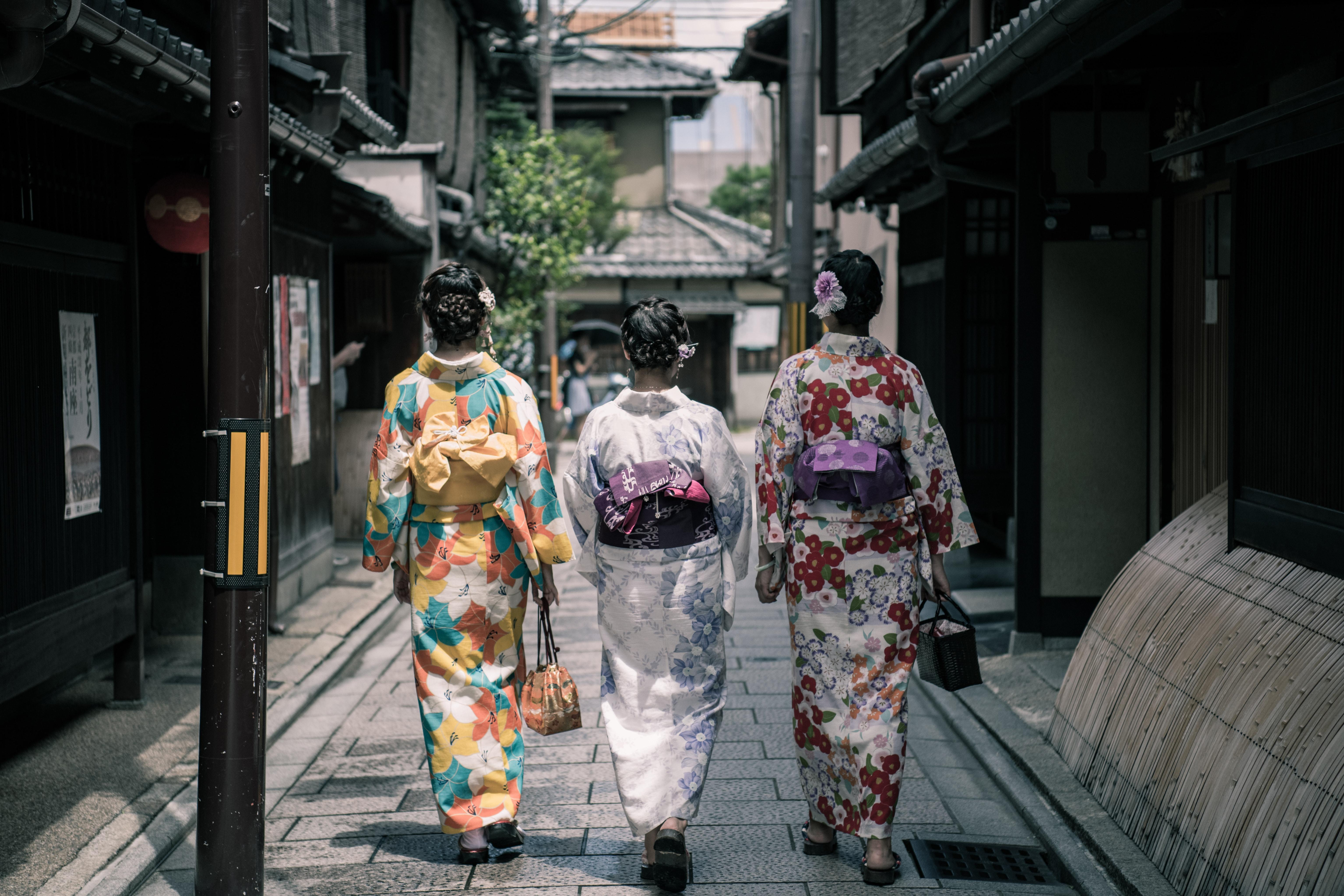 Geishas walk with closed kimonos