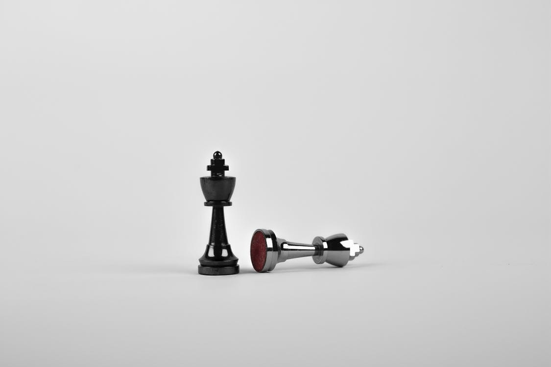 A chess pawn topples another one, symbolizing the replacing of a debtor's management with a chapter 11 trustee